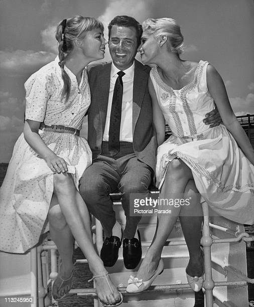 British actor Dirk Bogarde is greeted by Melissa Bassler and Penny Hollweger of the Radio City Music Hall Rockettes upon his arrival in New York for...