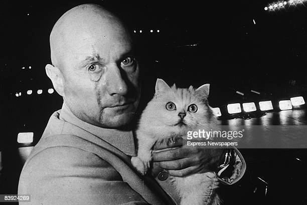 British actor Donald Pleasence in character as Ernst Stavro Blofeld holding a white cat on the set of the James Bond film 'You Only Live Twice' 24th...