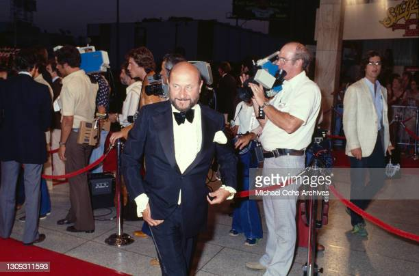 British actor Donald Pleasence, wearing a tuxedo over a white shirt with a bow tie, walks the red carpet with camera operators in the background at...