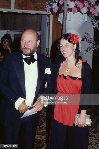 British actor Donald Pleasence, wearing a tuxedo over a white shirt with a bow tie, and his wife, Meira Shore, wearing a red top with black trim...