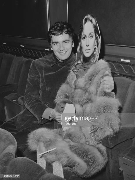 British actor Dudley Moore attends the premiere of '30 is a Dangerous Age Cynthia' with a life size cardboard model of his wife actress Suzy Kendall...