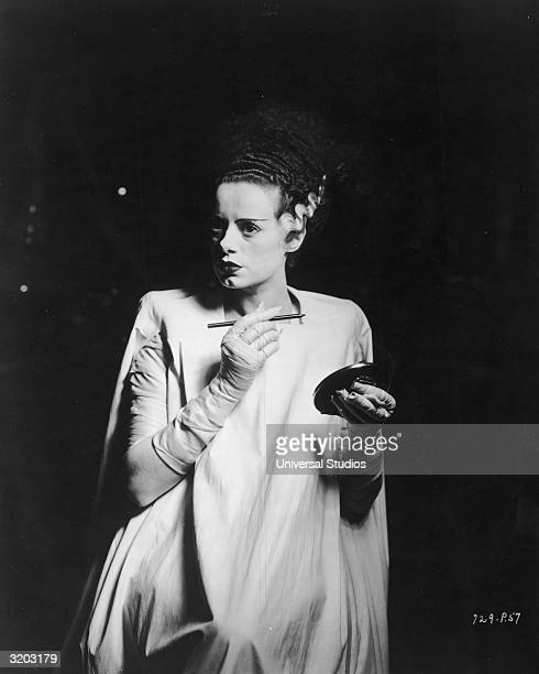 British actor Elsa Lanchester stands in a spotlight surrounded by darkness while holding an eyebrow pencil and a compact mirror on the set of...
