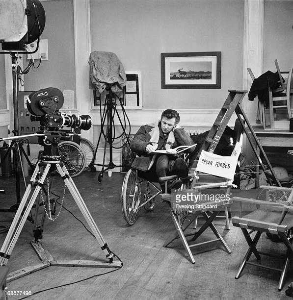 British actor, film director and writer Bryan Forbes sitting in a wheelchair on the set of his film 'The Raging Moon', UK , February 1970.