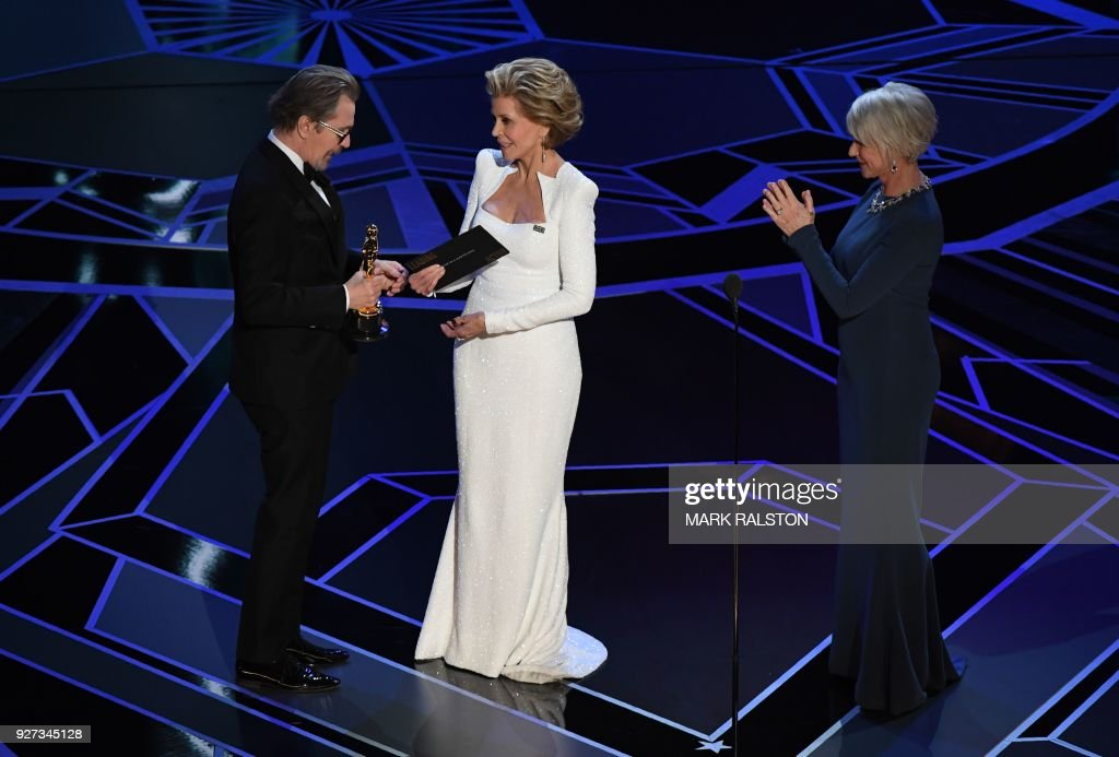British actor Gary Oldman accepts the Oscar for Best Actor in 'Darkest Hour' from US actress Jane Fonda (C) and British actress Helen Mirren during the 90th Annual Academy Awards show on March 4, 2018 in Hollywood, California. / AFP PHOTO / Mark RALSTON