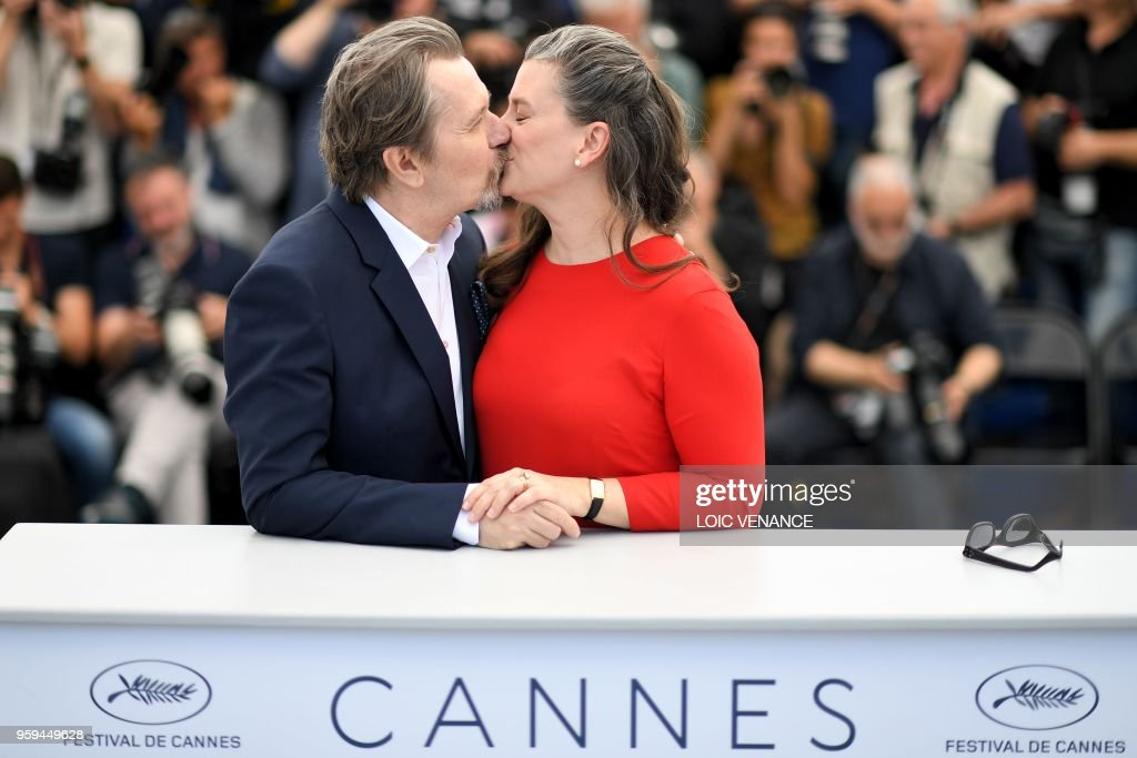 British actor Gary Oldman (L) kisses his wife Gisele Schmidt on May 17, 2018 during a 'Rendez-Vous with Gary Oldman' at the 71st edition of the Cannes Film Festival in Cannes, southern France.