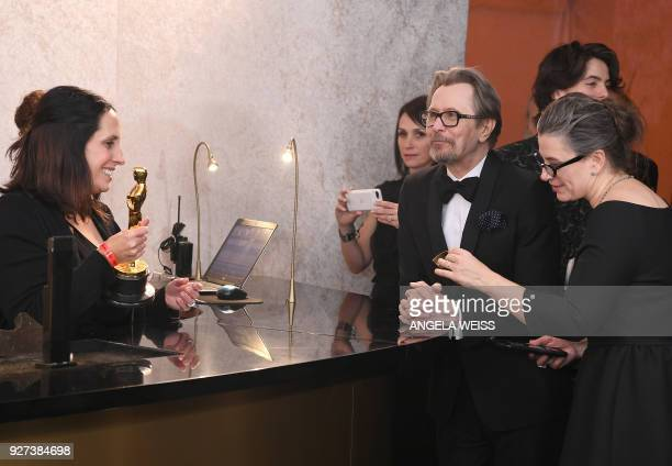 British actor Gary Oldman winner of Best Actor for Darkest Hour looks at the Oscar during the 90th Annual Academy Awards on March 4 in Hollywood...