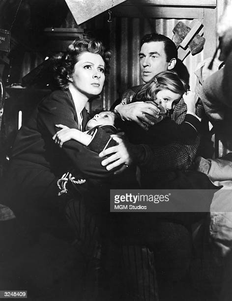 British actor Greer Garson and Walter Pidgeon hold frightened Christopher Severn and Clare Sandars while they all take cover during an air raid in a...