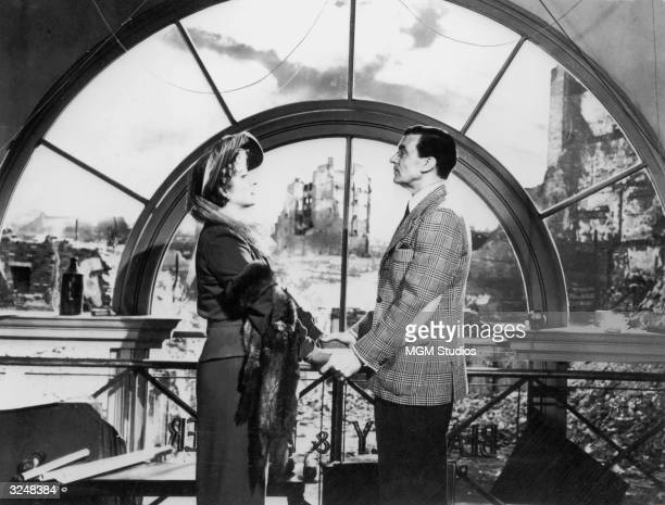 British actor Greer Garson holds hands with Canadian actor Walter Pidgeon in front of a window overlooking wartorn London streets in a still from the...
