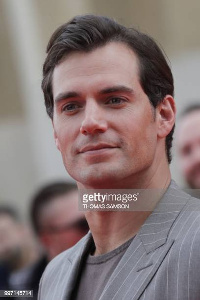 British actor Henry Cavill poses on the red carpet as he arrives to attend the world premiere of his new film Mission Impossible Fallout on July 12...