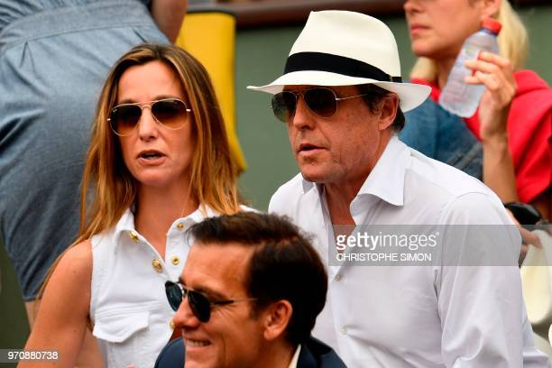 British actor Hugh Grant and Anna Eberstein look on ahead of the men's singles final match between Spain's Rafael Nadal and Austria's Dominic Thiem...