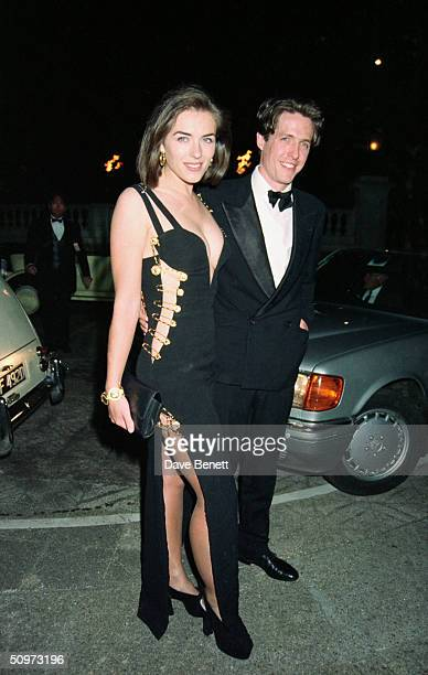 "British actor Hugh Grant and his girlfriend Elizabeth Hurley attend the premiere of ""Four Weddings And A Funeral"" on May 11, 1994 in London, England."