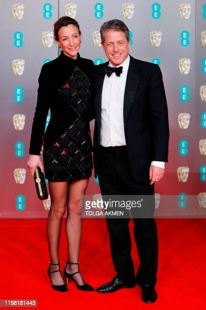 British actor Hugh Grant and his wife Anna Elisabet Eberstein pose on the red carpet upon arrival at the BAFTA British Academy Film Awards at the...