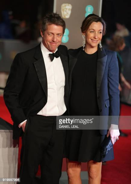 British actor Hugh Grant and producer Anna Eberstein pose on the red carpet upon arrival at the BAFTA British Academy Film Awards at the Royal Albert...