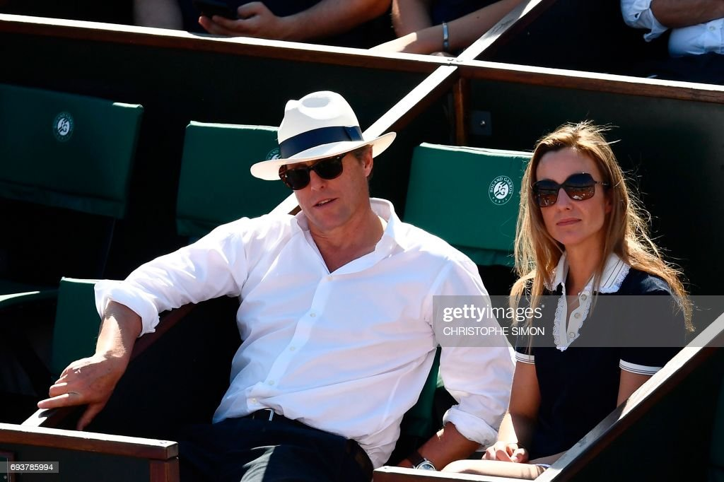 British actor Hugh Grant (L) and Swedish producer Anna Elisabet Eberstein attend the semifinal tennis match between Latvia's Jelena Ostapenko and Switzerland's Timea Bacsinszky at the Roland Garros 2017 French Open on June 8, 2017 in Paris. /