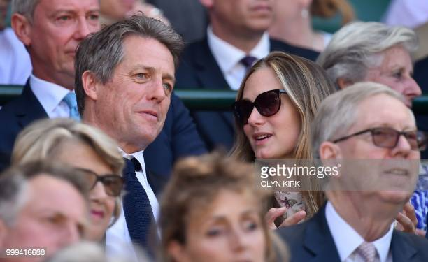 British actor Hugh Grant sits in the Royal Box before South Africa's Kevin Anderson plays Serbia's Novak Djokovic in their men's singles final match...
