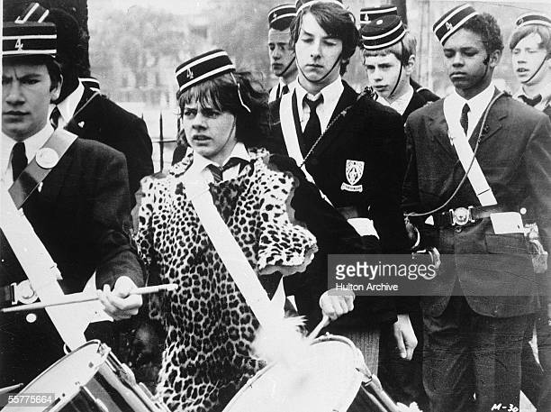 British actor Jack Wild wears a leopardskin smock as he plays the drums in a marching band in a still from the film 'Melody' directed by Waris...