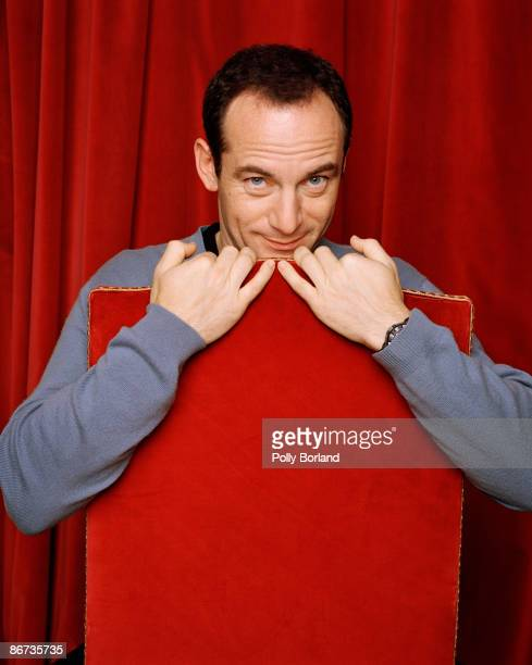 British actor Jason Isaacs peers out from behind a red cushion circa 2005