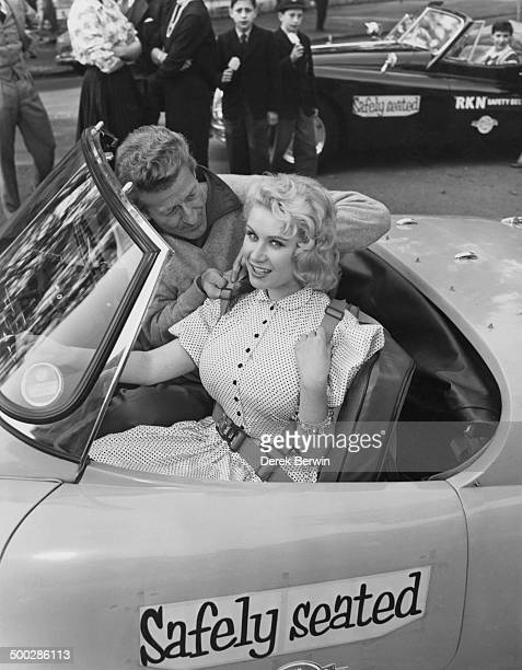 British actor Jon Pertwee adjusts the safety harness of model Rita Royce as they prepare to take part in a parade from Rotten Row to Hendon to...