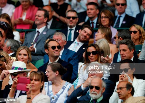 British actor Jude Law and his wife Phillipa Coan and British actor Hugh Grant sit in the Royal Box above Centre Court before the start of the men's...