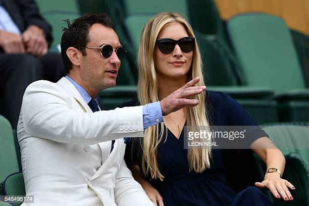 British actor Jude Law and partner Phillippa Coan sit in the royal box on centre court before the men's semifinal match on the tweflth day of the...