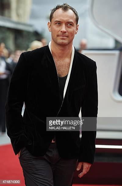 British actor Jude Law poses for photographs on the carpet as he arrives to attend the European premiere of the film 'Spy' in London on May 21 2015...
