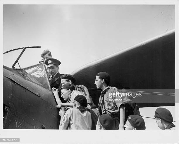 British actor Laurence Olivier sitting in the cockpit of an Albacore aircraft showing a group of scouts how everything works at a Fleet Air Arm...