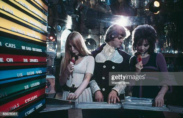 British actor Malcolm McDowell meets two girls in a record store in a scene from 'A Clockwork Orange' 1971