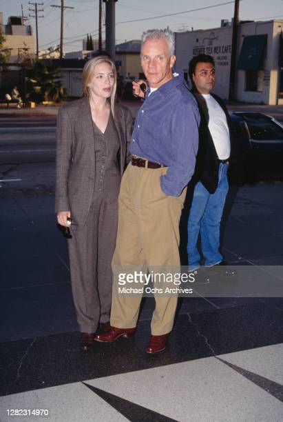 British actor Malcolm McDowell, wear tan trousers and a blue shirt over a white t-shirt, and his wife Kelley Kuhr, wearing a grey tweed trouser suit,...
