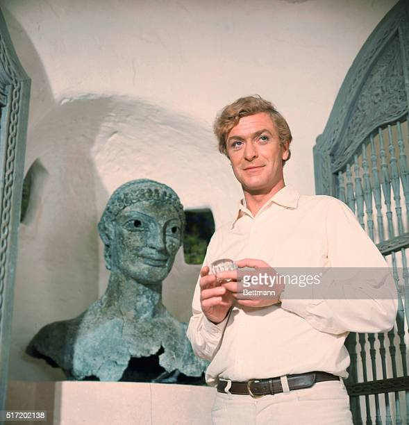 British actor Michael Caine, , in an unidentified movie. He wears a white shirt with white trousers and stands next to a bronze Etruscan bust.