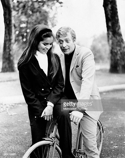British actor Michael Caine rides a bike with the girlfriend Nicaraguan model Bianca De Macias sitting on the handlebar and smile amused Turin August...