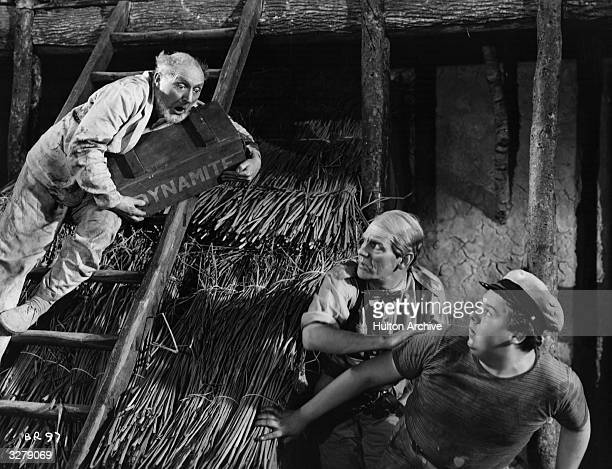 British actor Moore Marriott is halfway up a ladder about to drop a large case of dynamite onto his colleagues Graham Moffatt and Will Hay in a scene...