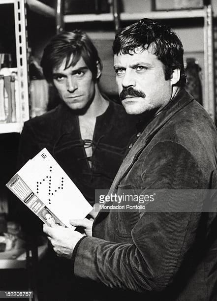 British actor Oliver Reed holding a puzzle magazine next to Italian actor Fabio Testi on the set of 'Revolver' 1973