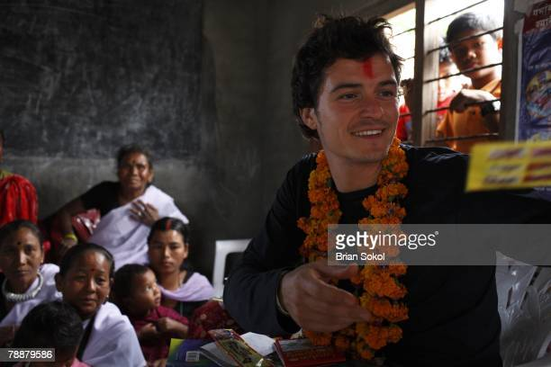 British actor Orlando Bloom wearing flower garlands and a red tikka mark on his forehead visits ethnic Tharu children and women at the Sayapatri...