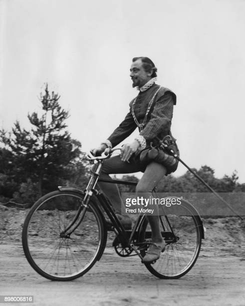 British actor Patrick Cargill uses an anachronisticlooking bicycle to get from one part of the set to the next during the filming of the BBC...
