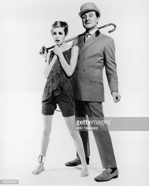 British actor Patrick MacNee, in costume as secret agent John Steed, and British model Twiggy pose for a publicity photograph promoting MacNee's...