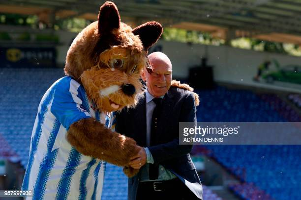 TOPSHOT British actor Patrick Stewart poses for a photograph with Huddersfield mascot Terry the Terrier on the pitch ahead of the English Premier...
