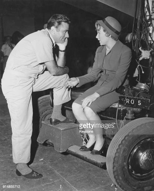 British actor Peter Lawford listens to costar Shirley MacLaine on a movie set circa 1960