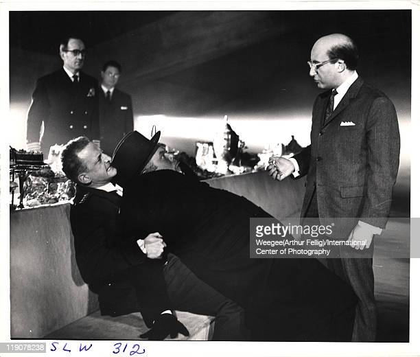 British actor Peter Sellers talks to actor Peter Bull , who is restrained by American actor George C. Scott , in the War Room set of the movie 'Dr....