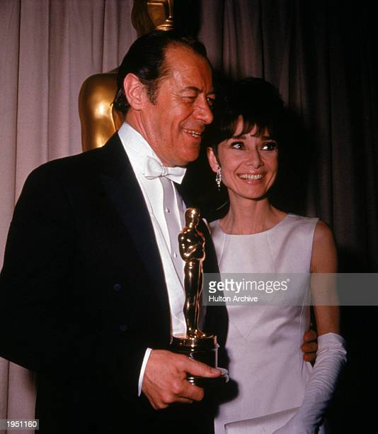 British actor Rex Harrison holds his Best Actor Oscar for the film 'My Fair Lady' while standing with his costar actor Audrey Hepburn during the...