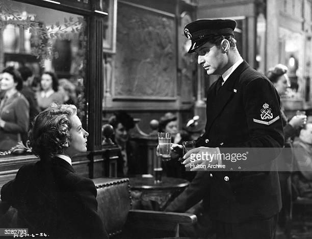 British actor Robert Donat meets his screen wife Deborah Kerr in a London pub three years after he went into the Navy in a scene from 'Perfect...