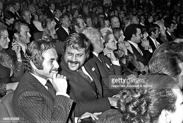 British actor Robert Oliver Reed sitting in the parterre of the Teatro Sistina and talking to a man On his left there is the Italian director...
