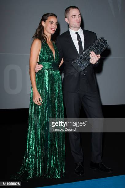 British actor Robert Pattinson receives an achievement tribute award from french actress Berenice Bejo during the 43rd Deauville American Film...