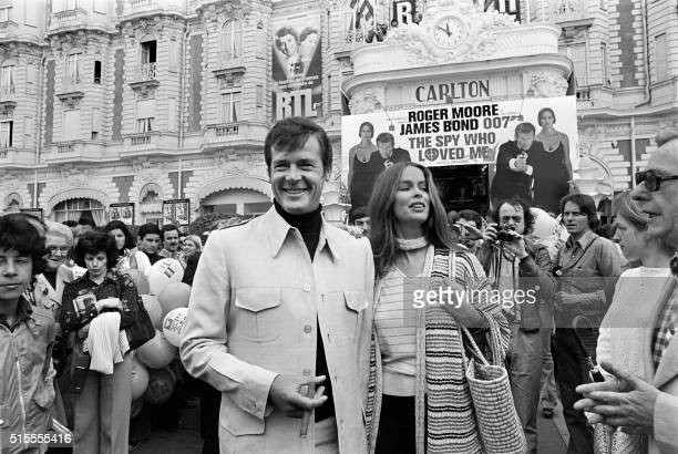 "British actor Roger Moore and US actress Barbara Bach pose outside the Carlton Hotel for the presentation of the film ""The spy who loved me"" during..."