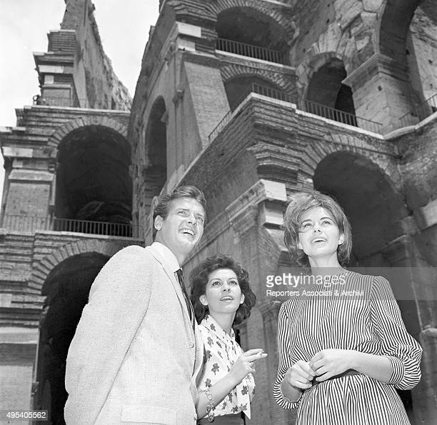 British actor Roger Moore Italian actress Luisa Mattioli and Italian actress and singer Giorgia Moll visiting the Colosseum in a break on the set of...