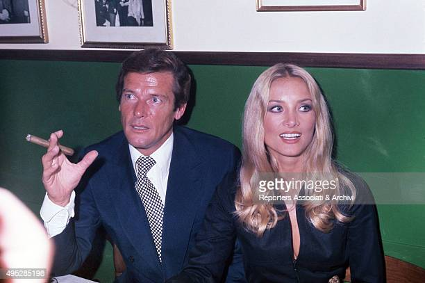 British actor Roger Moore sitting beside Germanborn Italian actress Barbara Bouchet and holding a cigar at a dinner 1973