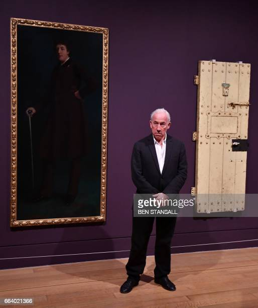 British actor Simon Callow poses with Oscar Wilde's Prison Door c1883 and an oil painting entitled 'Oscar Wilde' c1881 by US artist Robert Harper as...