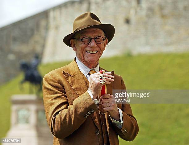 British actor Sir John Hurt poses after being awarded a knighthood by Queen Elizabeth II during an Investiture ceremony at Windsor Castle on July 17...