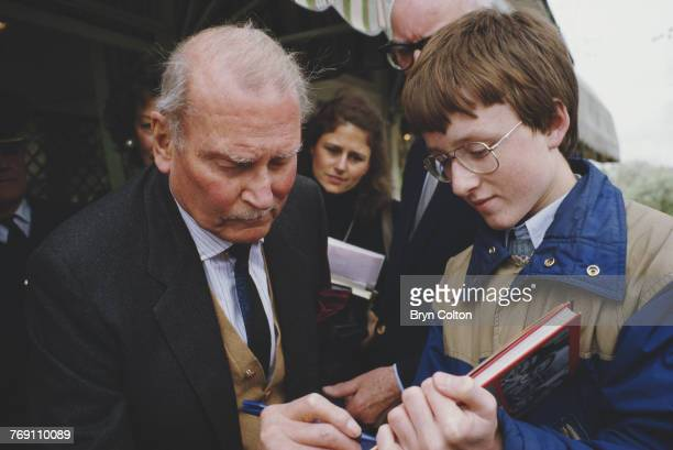 British actor Sir Laurence Olivier signs an autograph for a fan after unveiling a bronze relief sculpture of himself by Lawrence Holofcener at...