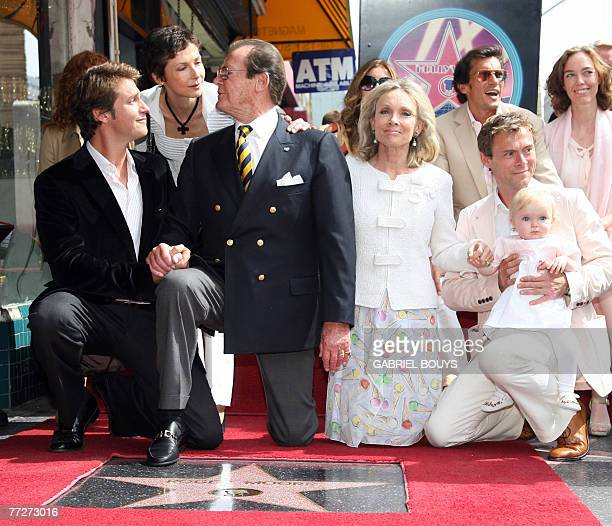 British actor Sir Roger Moore poses his family after being honored with a Star on the Hollywood Walk of Fame 11 October 2007 in Hollywood California...
