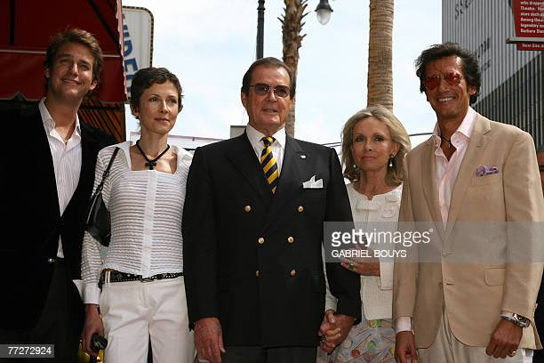 British actor Sir Roger Moore poses with his wife actress Christina Tholstrupafter and children Geoffrey Deborah and Christian after being honored...